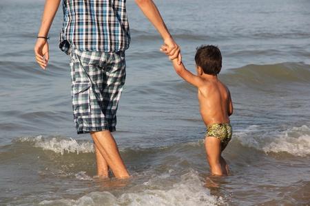 father leading son in sea Stockfoto