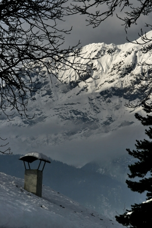 close up chimney: snow-covered chimney in the background mountains