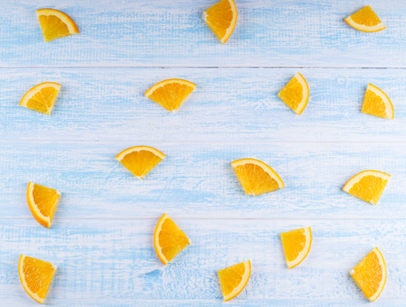 quartered: quartered of an orange background. Orange on blue wooden background top view. Overhead shot of oranges on an old wooden table