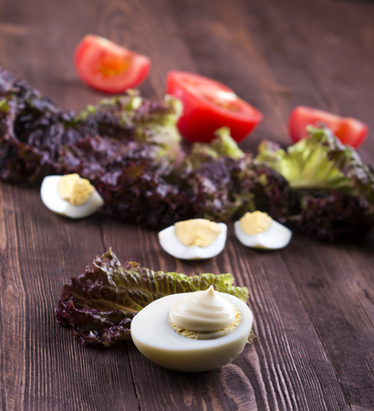 half of boil egg handful of mayonnaise.  egg, tomato, lettuce on a wooden background. Stock Photo