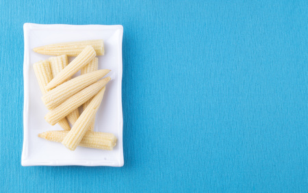mini corn, canned lies on a rectangular white plate on a blue background Banco de Imagens