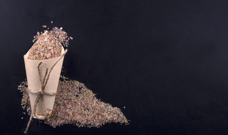 Himalayan salt with spices in a paper bag on a black background. Stock Photo