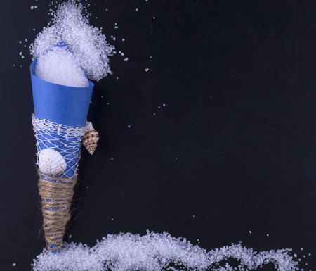Sea salt in a blue paper bag is scattered on a black background. Sol Ornamental package. Stock Photo