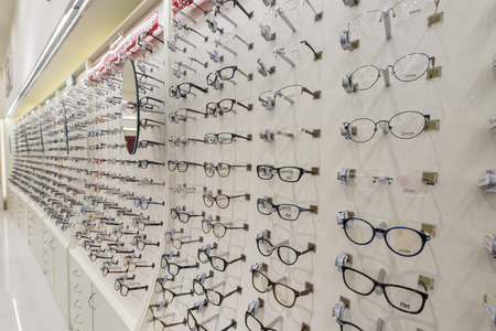 Optical shop. Optician suggest glasses. Closeup showing many eyeglasses in background.