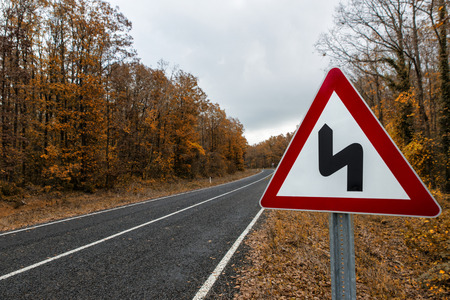 traffic sign on the forest road in the autumn Stock Photo