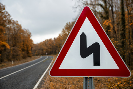 traffic sign on the forest road in the autumn Stock fotó