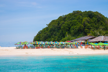 ful: Colorful sunshade and chairs on beach in Phuket