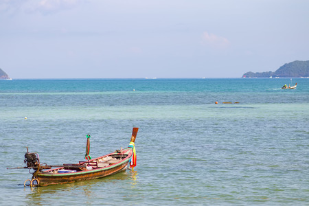water scape: Long-tail boat parked in a calm sea.rawai beach,phuket,thailand.