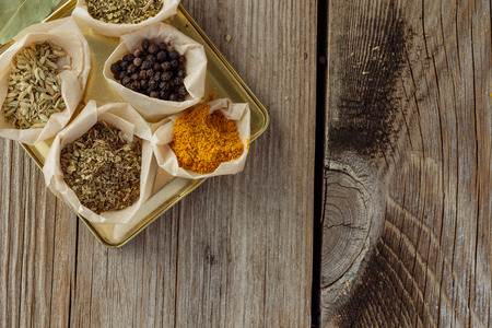 wooden table top view: Different herbs and spices on wooden table top view