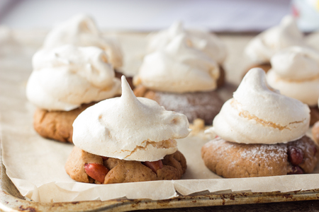 kiss biscuits: Shot of shortbread cookies with peanut and meringues on cooking paper Stock Photo