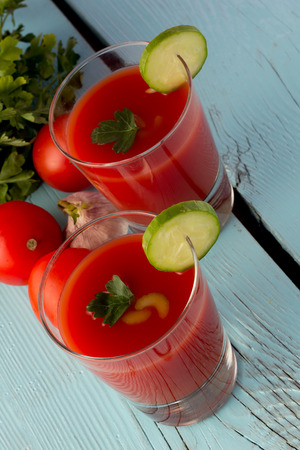 gaspacho: Shot of tomato gazpacho in glasses over blue wooden table vertical