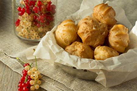 puffs: Cream puffs in cooking paper and currant selective focus