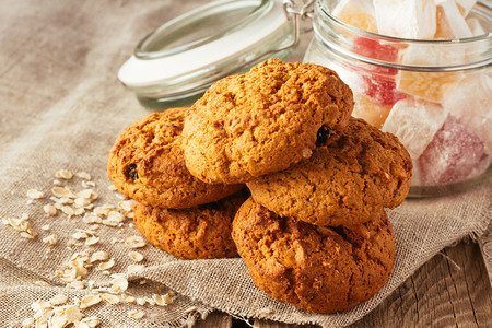 oatmeal cookies: Oatmeal cookies and jar with sweeties on linen cloth selective focus