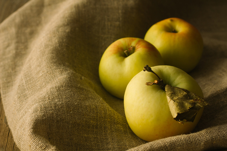 green yellow: Tree apples on linen cloth selective focus horizontal Stock Photo