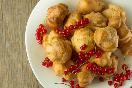 puffs: Cream puffs and red currant on white plate selective focus horizontal top view Stock Photo