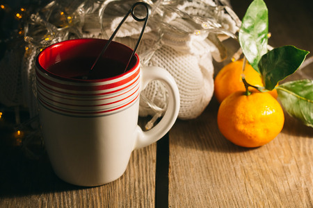 rustic christmas: Cup of tea, pullover, tangerine in a low key selective focus Stock Photo