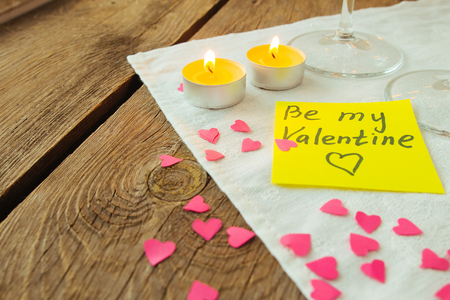 saint valentines: Yellow sticky note for Saint Valentines day and little pink paper hearts selective focus