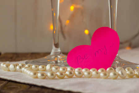 love confession: Pink paper heart with love confession and pearls selective focus