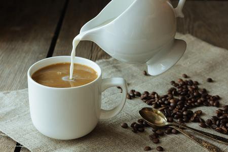 Milch, die in den selektiven Fokus des Tasse Kaffees gießt Standard-Bild