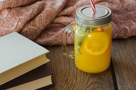 glass jar: Orange drink in glass jar and books selective focus