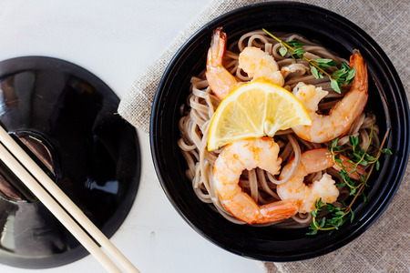 Soba with shrimps and herbs top view selective focus