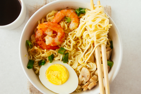 Noodles with shrimps, mushrooms and egg selective focus top view Stock Photo