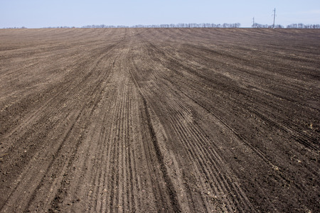 ploughed: black ploughed field under blue sky