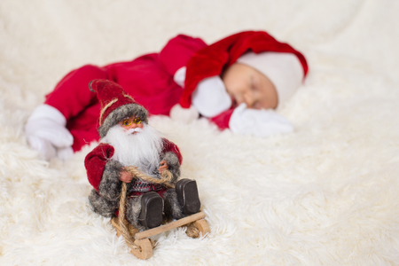 The image of a cute baby sleeping in Christmas clothes Stock Photo
