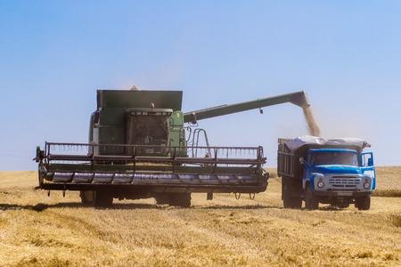 john deere: Khmelnitskiy, Ukraine - July 23: Modern John Deere combine harvesting grain in the field near the town Khmelnitskiy, Western Ukraine July 23, 2015
