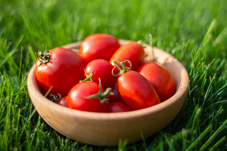An images of red tomatoes on a wooden plate