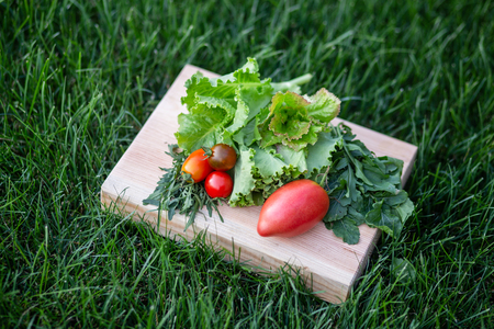 An image of lettuce, arugula leaves, tomatoes on a wooden plate