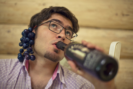 A young man with grapes behind the ear drinks wine from a bottle