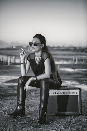 A brutal girl smokes a cigarette while sitting on the amplifier. Portrait of rock star young woman