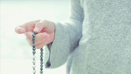 Woman, lit hand close up, counts Malas, strands of gemstones beads used for keeping count during mantra meditations. Stockfoto