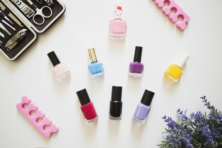 colorfull: Beautiful colorful nail polishes and instruments for manicure on white table. top view. Stock Photo