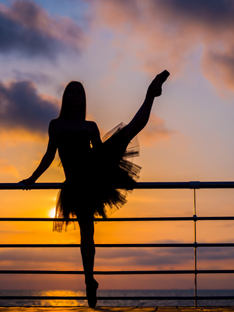 pies bailando: Silhouette of dancing ballerina in black ballet tutu and pointe on embankment above ocean or sea at sunrise or sunset. Young attractive blonde woman with long hair practicing stretching and exercises.