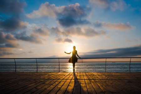 long: Silhouette of dancing ballerina in black ballet tutu and pointe on embankment above ocean or sea at sunrise or sunset. Young attractive blonde woman with long hair practicing stretching and exercises.