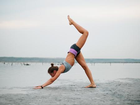 Healthy life exercise concept - Young sporty fit woman doing yoga Sun salutation Surya Namaskar pose Hasta Uttanasana on beach on sunset. Imagens