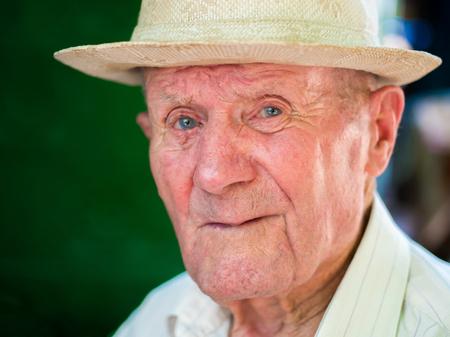 Retrato muito velho com emoções. Avô feliz e sorridente. Retrato: idoso, idoso sênior. Close-up de um homem idoso pensativo no chapéu branco que senta-se sozinho ao ar livre no verão.