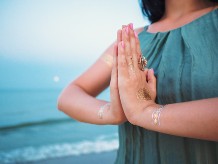 Silver and golden flash tattoo on female hands over sea or ocean background. Woman practicing yoga. Namaste Stock Photo
