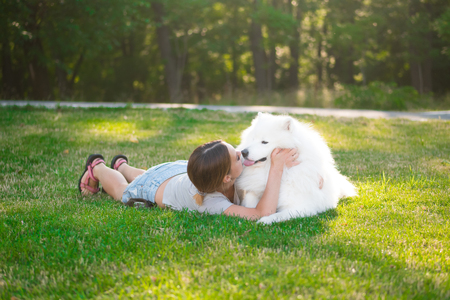 An adult woman with red hair plays and strokes her dog of the Samoyed breed. White fluffy pet in a park with mistress on a green lawn have fun.