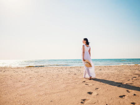 Girl wearing white maxi long dress walking barefoot on the sea shore with hat in hands. Bohemian clothing style.