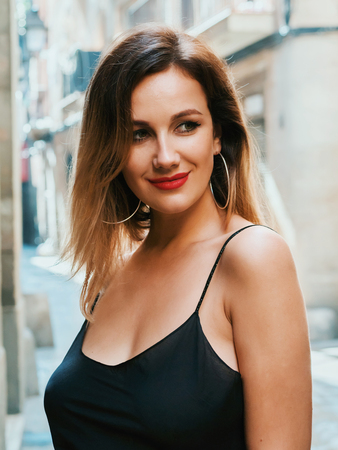 Gorgeous blonde alluring woman in sexy black dress and red lips walking in gothic quarter of Barcelona. Natural beauty, female portrait, seductive look. Being self-confident.