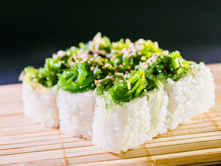 Sushi with Green Seaweed Chukka and Omelet Isolated on Black. Susi background