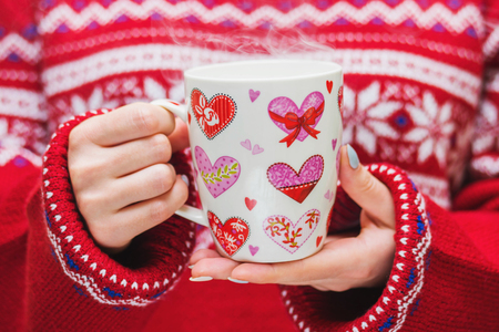 Woman in red sweater holds a winter cup with hearts close up. Winter and Christmas time concept.