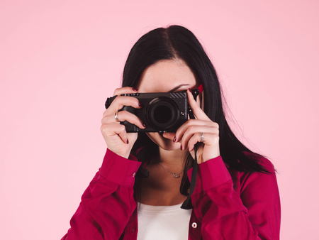 Young pretty brunette woman in pink shirt takes pictures with DSLR camera over colorful background in studio. Girl smiling, flirting and having fun as photographer.