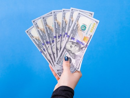 Woman hand with dollars isolated on blue background
