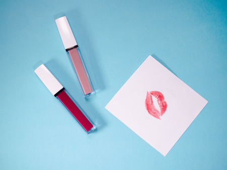 beautiful beige and red glosses, paper with lip print, isolated on blue background.