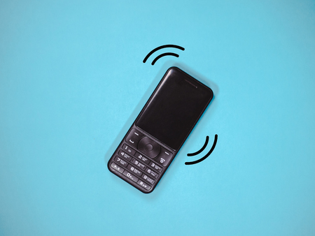Old mobile telephone is ringing isolated on blue background. Stock Photo