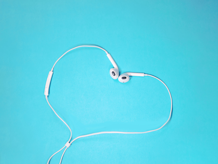 white earphones heart shaped on a blue background. Music concept. Copy space